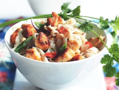 A white bowl of pad Thai noodles topped with green onions, chilis, Quorn Pieces and a sprig of cilantro.