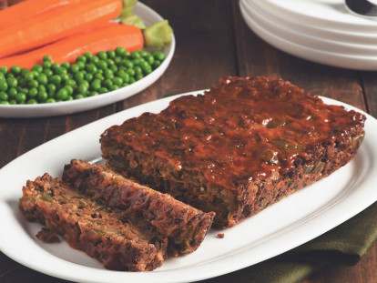 A meatloaf made with Quorn Grounds on a white plate with peas and carrots in the background.