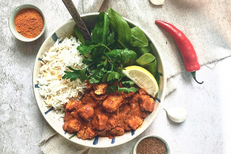 Quorn Vegan Masala Curry, made with Quorn Vegan Pieces, onion, turmeric, paprika, chilli, served with rice, lettuce and lemon in a bowl.