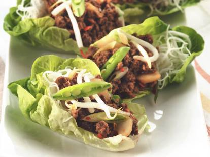 Three lettuce cups filled with Quorn Meatless Grounds, water chestnuts, and rice noodles, topped with bean sprouts and snow peas served on a white plate.