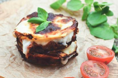 A circular, bite-sized stack of lasagna, Quorn Grounds, and cheese topped with basil and garnished with a halved cherry tomato.