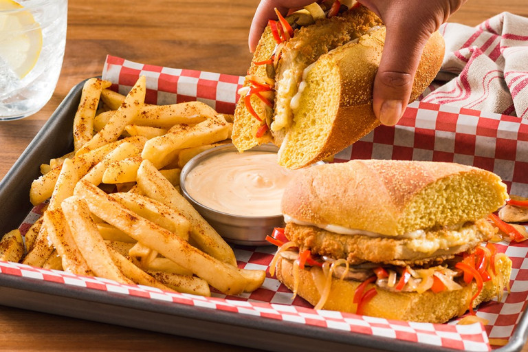 Meat-free Hoagie on tray with chips and dipping sauce