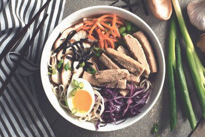Soup noodles made with Quorn Fillets, carrot, edamame beans, cabbage and half an egg served on top of noodles in a bowl