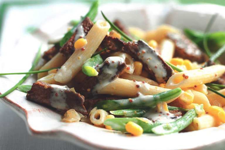 A serving of vegetarian creamy mustard pasta made with Quorn Vegetarian Steak Strips, fresh vegetables, and penne pasta in a white bowl.