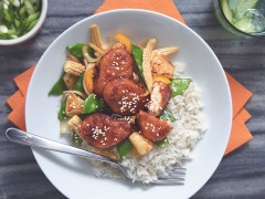 Quorn Nuggets, baby corn, pineapple, onions, and snow peas topped with a glaze and sesame seeds atop a bed of white rice on a white plate.
