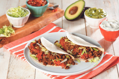 Two flour tortilla tacos filled with Quorn Grounds, shredded lettuce, and diced tomatoes on a white plate surrounded by a variety of toppings.
