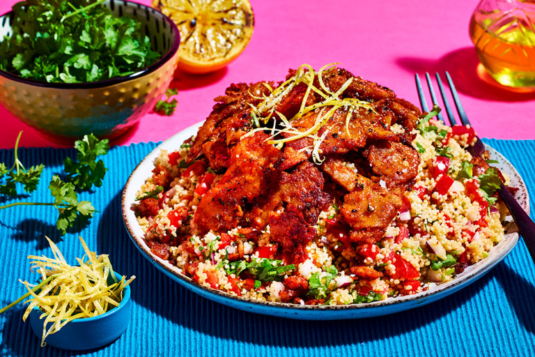 A couscous salad with red onion, red pepper, and tomato topped with Quorn Makes Amazing Peri Peri Strips on a turquoise placemat against a fuchsia background.