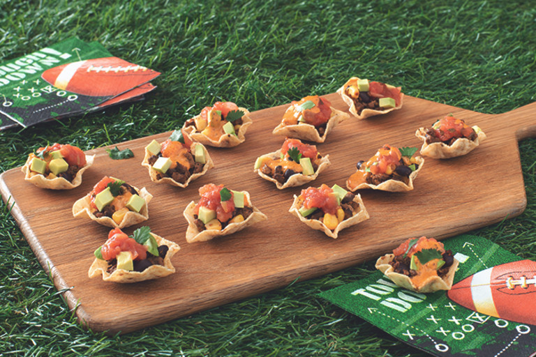 Mini Tortilla Chip Bowls Filled with Quorn Grounds, black beans, salsa, queso, avocado, and cilantro arranged on a board with game day napkins placed around it.