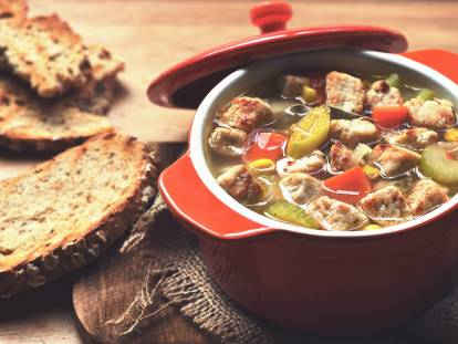 A vegetable soup with carrots, celery, sweetcorn, and Quorn Pieces in a red Dutch oven with toasted wholegrain bread on the side.