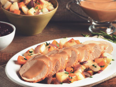 Sliced Quorn Meatless Vegetarian Turkey Roast topped with gravy with roasted root vegetables on the side on an oblong-shaped white plate.