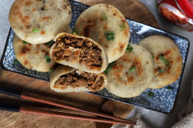 Six vegetarian air fryer kimchi buns arranged on a plate with one halved to reveal a filling of Quorn Mince and kimchi.