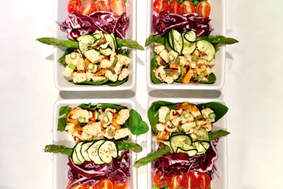 Meal prep idea of Quorn Pieces on top of asparagus, spinach, courgette and red cabbage, topped with chopped spring onion