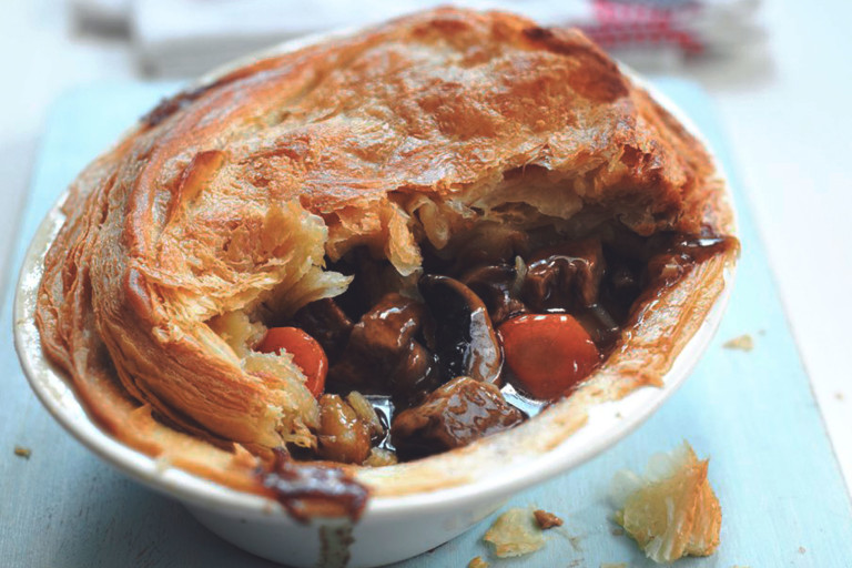 A vegetarian steak and ale pie made with Quorn Vegetarian Steak Strips, mushrooms, and a puff pastry top in a white baking dish.