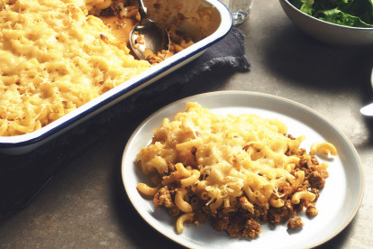 A portion of Quorn Grounds topped with macaroni and cheese on a white plate with the baking dish of the rest of the macaroni and cheese in the background.