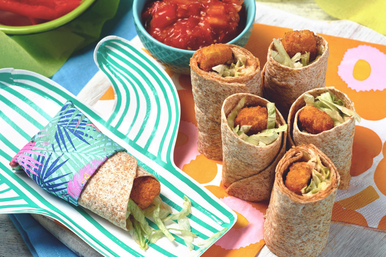 Wholegrain wraps filled with Quorn Fishless Sticks and shredded lettuce, sliced in half and arranged on a colorful serving tray.