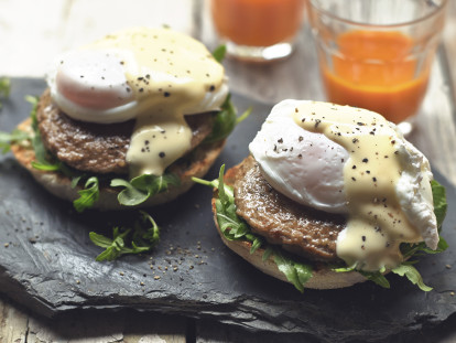 Eggs Benedict made with an English muffin topped with arugula, Quorn Sausage Patties, a poached egg, Hollandaise sauce, and freshly-ground black pepper.
