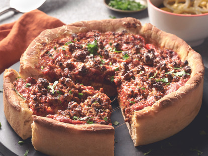 Chicago-Style Deep Dish Pizza topped with Quorn Meatless Grounds and cheese, on a black dish alongside an orange napkin and bowls of toppings like jalapenos.