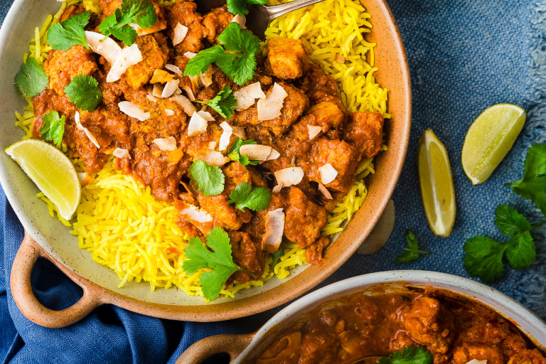 A vegetarian rogan josh curry made with Quorn Pieces topped with dried coconut and coriander atop a bed of saffron rice with a wedge of lemon on the side.