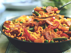 A paella made with Quorn Sausages, peppers, and green beans in a pan.