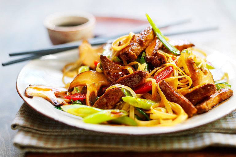 A serving of vegetarian teriyaki noodles made with Quorn Vegetarian Steak Strips, mixed vegetables, and teriyaki sauce on a white plate with chopsticks on the side.