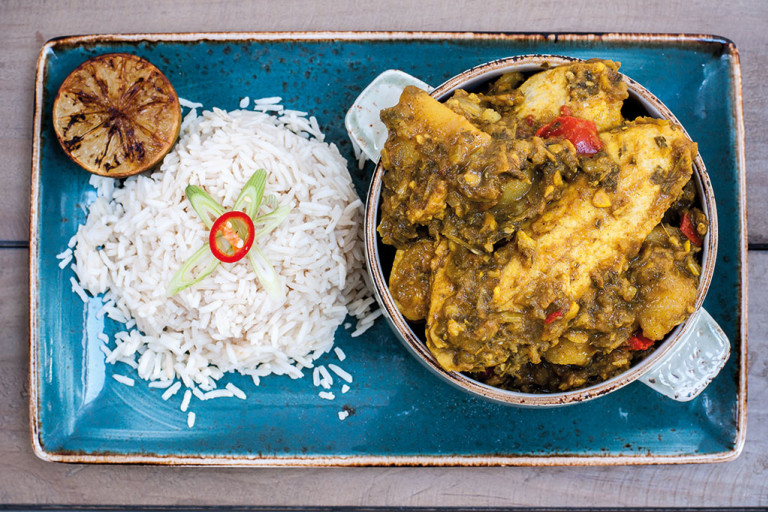 A mini cocotte of Trini curry chicken made with Quorn Vegan Pieces served with a side of rice and half of a charred citrus on a blue tray.