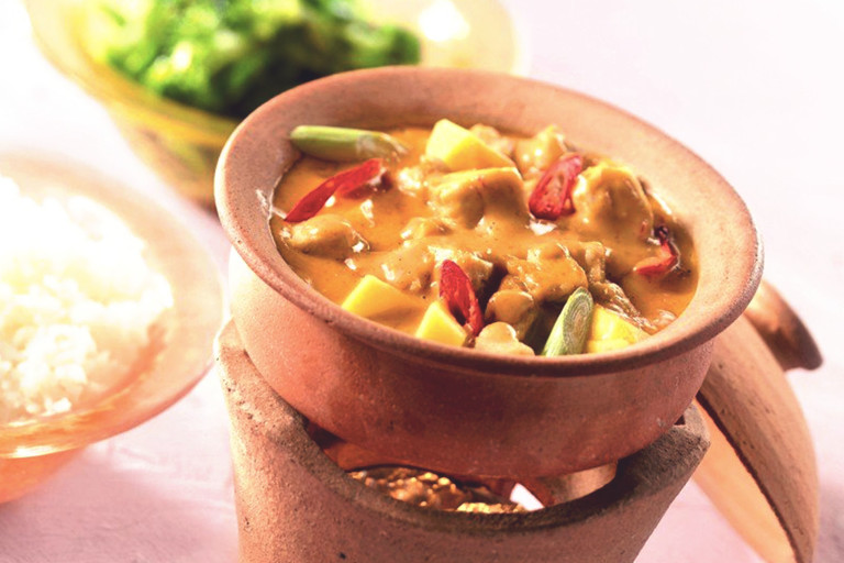 Vegetarian Thai red curry made with Quorn Pieces, peppers and mango served in a ceramic dish next to a bowl of rice