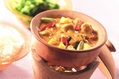A red curry with lemongrass, mango, and Quorn Pieces in a terra cotta bowl with a bowl of rice on the side.