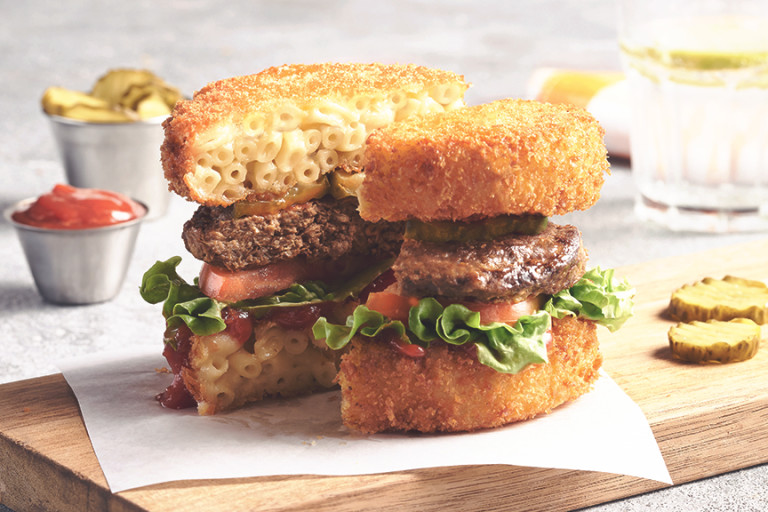 A veggie burger topped with lettuce, tomatoes, pickles, and ketchup with two breaded patties of macaroni and cheese as a bun, served on a plank.
