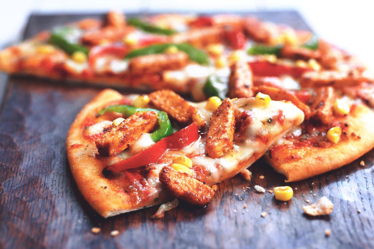 A pizza topped with cheese, red and green peppers, corn, and Quorn Pieces.