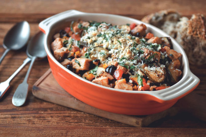 An orange baking dish filled with eggplant, zucchini, tomatoes, and Quorn Pieces topped with breadcrumbs and basil.