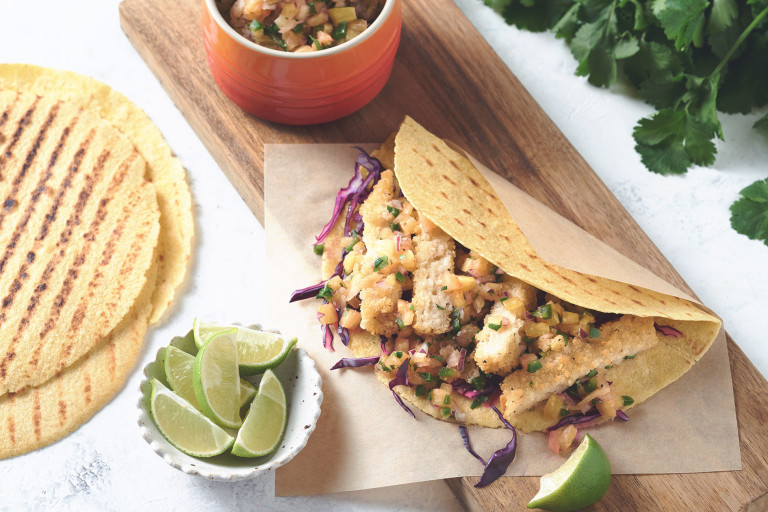 A lemon pepper vegan fish taco served with shredded red cabbage and accompanied with a tangy pineapple salsa