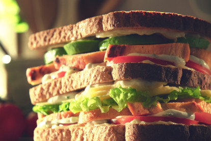 A double-decker sandwich filed with lettuce, tomatoes, avocado, Quorn Fillets, and a yogurt dressing.