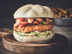 A Quorn fully loaded Cajun burger with relish in a warm bun and a bowl of French fries.