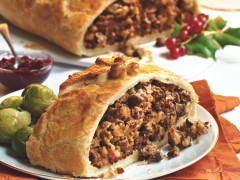 A slice of puff pastry filled with Quorn Grounds and mushrooms with Brussels sprouts on the side, and a chutney and the larger Wellington from which the slice has been taken in the background.