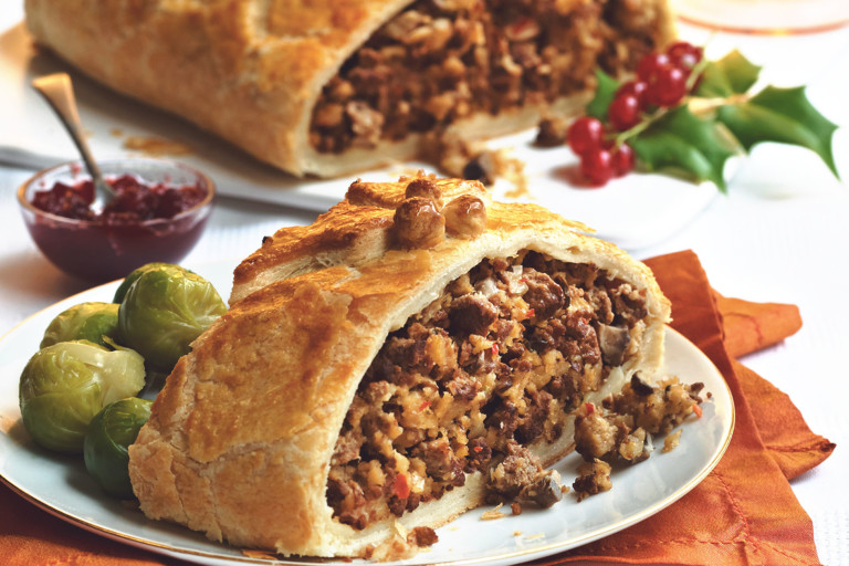 Vegetarian Wellington, made with Quorn Mince, onion, breadcrumbs, chilli, herbs, murshrooms, and served with sprouts, chutney on a plate.