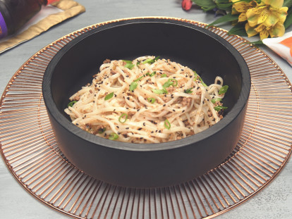 Thin noodles topped with sliced green onions, black and white sesame seeds, and Quorn Grounds in a dark bowl.