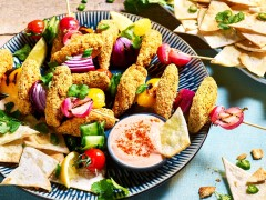 Quorn Sriracha Crumbed Tenders arranged on skewers with fresh vegetables with pita chips and bang bang sauce on the side.