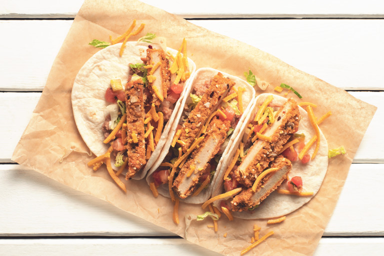 Veggie tacos made with Quorn Vegan Spicy Tortilla Escalopes, peppers and cheese in tortilla wraps served on baking paper