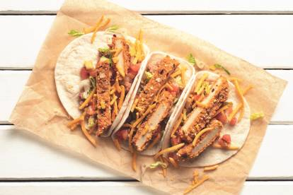 Three tacos in flour tortillas filled with sliced Quorn Vegan Meatless Chipotles Cutlets, cheese, refried beans, lettuce, and pico de gallo salsa on a piece of brown paper.