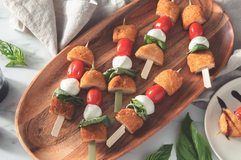 Skewers stacked with halved Quorn Crispy Nuggets, fresh mozzarella, cherry tomatoes, and basil.
