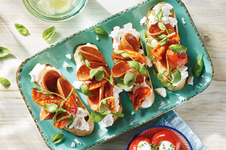 Four servings of vegan bruschetta topped with Violife Greek White Block, Quorn Vegan Pepperoni, sunblush tomatoes, and basil on a pale turquoise tray.