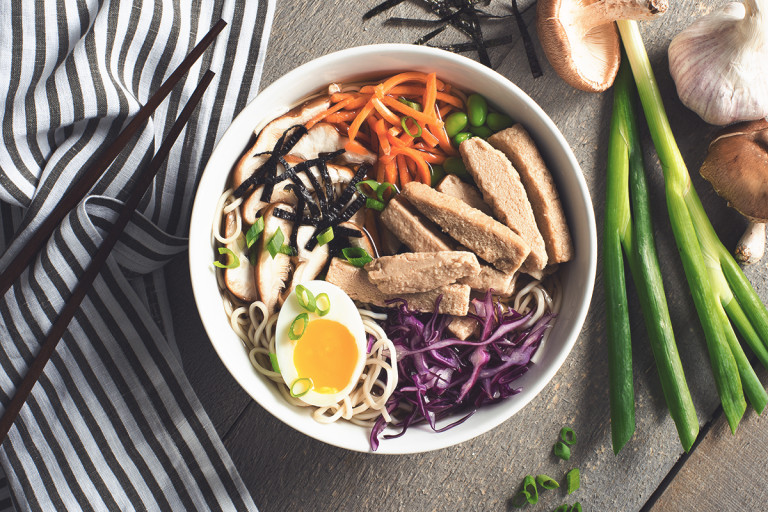 A bowl of ramen noodles topped with sliced mushrooms, edamame, shredded carrots, shredded purple cabbage, green onions, half of a half-cooked egg, nori, and Quorn Strips, with chopsticks and green onions on either side.