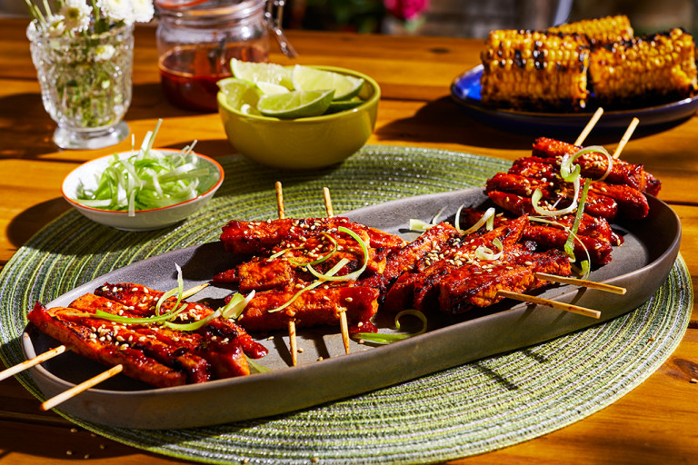 A platter with four servings of Korean BBQ Skewers made with Quorn Vegan Fillets topped with sesame and scallions.