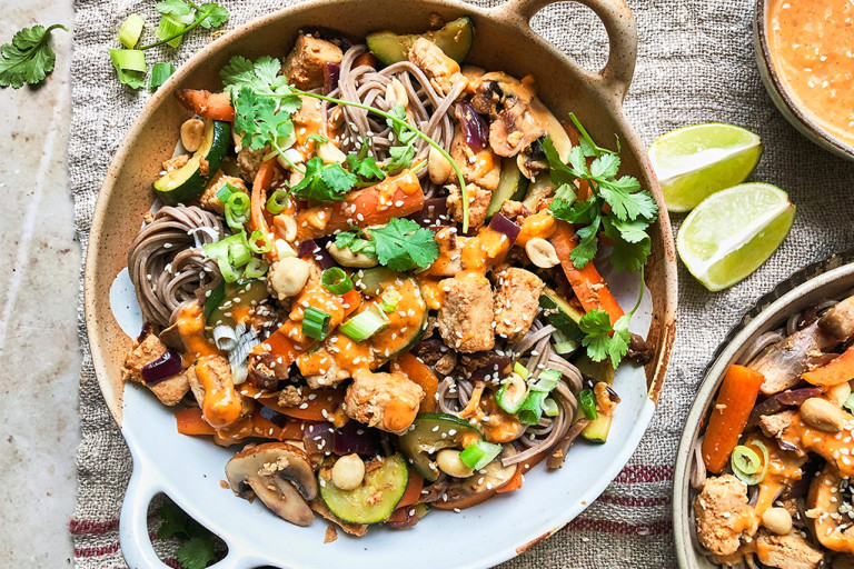 A bowl of vegan satay noodles topped with Quorn Vegan Pieces, carrots, mushrooms, courgette, green onions, peanuts, sesame seeds, coriander, and satay sauce.
