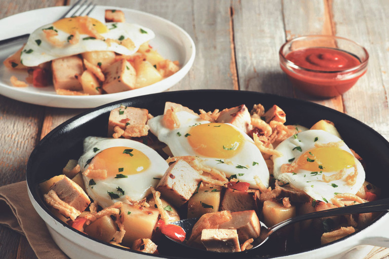 A skillet full of potatoes and cubed Quorn Meatless Roast topped with three fried eggs and crispy onions.