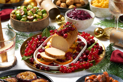 Cranberry and Orange Vegetarian Christmas roast made with a Quorn roast served on a dish, amongst a plate of cranberries and orange slides