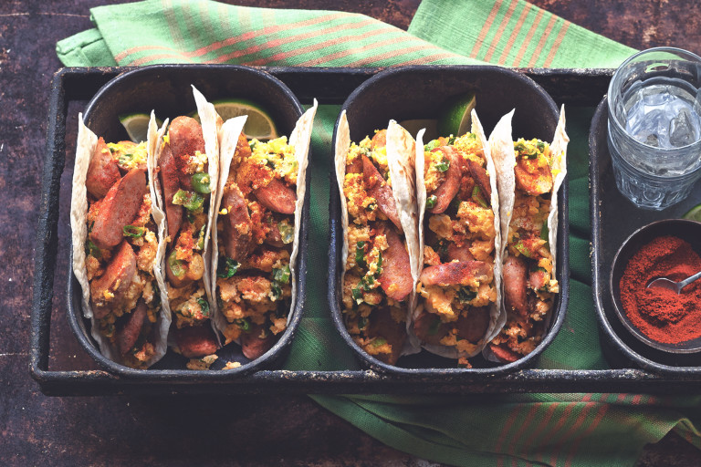 Two dishes of three flour tortilla tacos filled with Quorn Sausage, eggs, and cheese.