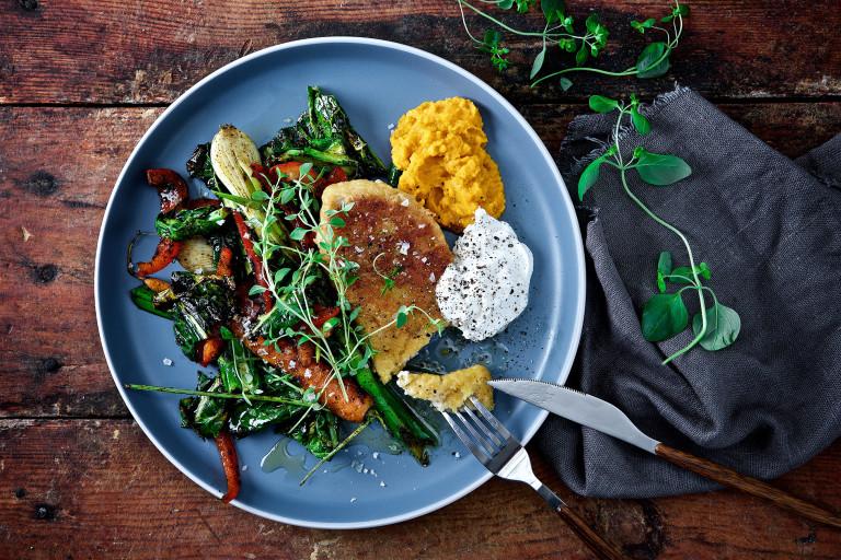 Panerad vegansk fisk med frästa grönsaker och morotshummus på tallrik.