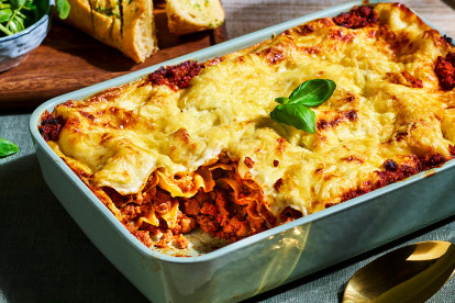 A white dish of vegetarian lasagna with Quorn Grounds with one portion already served to show the layers in the dish.