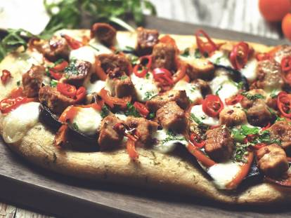 A flatbread pizza topped with cheese, eggplant, pepper, chile, and Quorn Pieces.